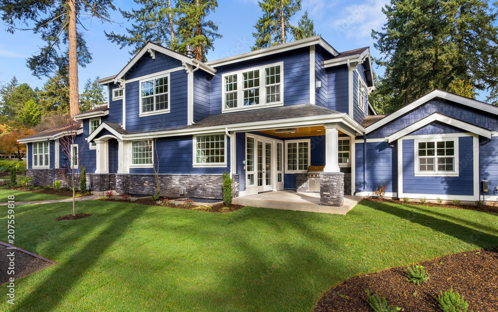 Fototapety, obrazy: Beautiful luxury home exterior on sunny day with green grass, blue sky, and backdrop of trees