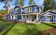 Beautiful luxury home exterior on sunny day with green grass, blue sky, and backdrop of trees