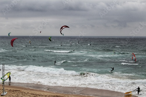 Surfers at Guincho beach under cloudy sky in Portugal