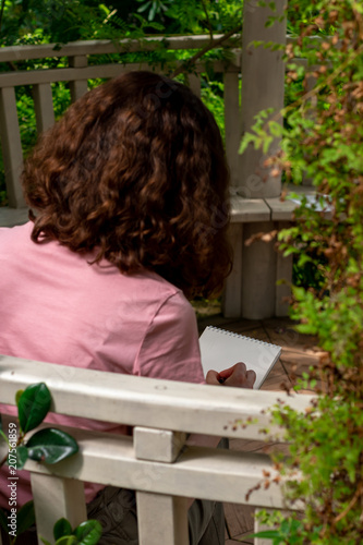 Fotografia  young girl draws in the garden