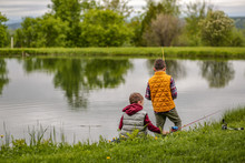 Children Fishing On The Shore Of The Lake. Brothers Hold Fishing Rods