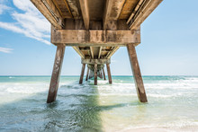 Under Okaloosa Fishing Pier In Fort Walton Beach, Florida During Day With Pillars, Green Shallow Waves In Panhandle, Gulf Of Mexico During Sunny Day