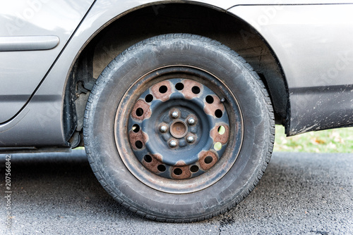 Fotografie, Obraz  Closeup of tire wheel with missing cap cover on parked car, rust, hubcap