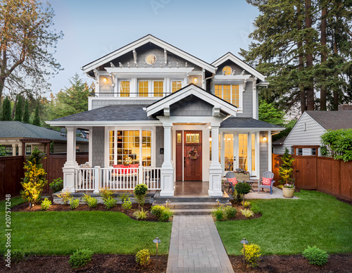 Beautiful Home Exterior At Dusk, with Green Grass, Covered Porch, and Glowing Interior Lights