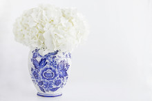 Photograph Of A Blue Delft Ginger Jar Filled With White Hydrangea On White