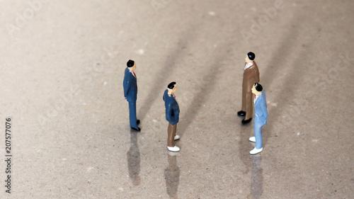 Four miniature men standing opposite. Canvas Print