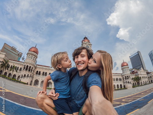 happy family makes selfie on the background on background of Merdeka square and Sultan Abdul Samad Building Wallpaper Mural