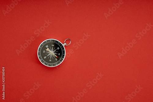 Fotografia  compass on red background top view