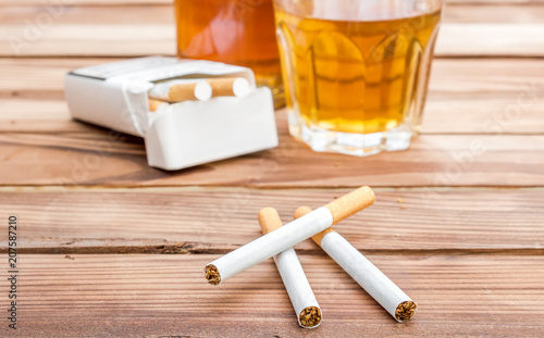 Poster de jardin Bar Cigarettes with alcohol drinks on wooden table. Social issues.