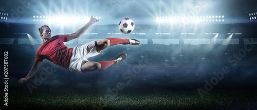 obraz dibond Soccer player in action on stadium background.