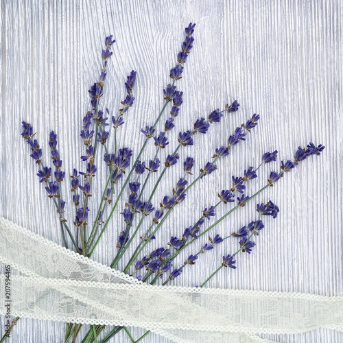 Small flowers of lavender with lace braid on gray wood background with copy space. Top view. Provans style photography