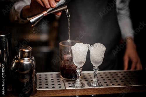 Fotografie, Obraz  Bartender pouring alcoholic drink into the glass for making fresh summer cocktai