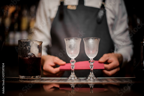 Bartender with two elegant cooled glasses arranged on the bar counter Canvas Print
