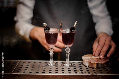 Photo Bartender with two elegant glasses filled with sweet summer Arnaud cocktail