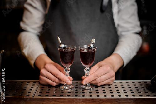 Fotografie, Obraz  Bartender holding two elegant glasses filled with sweet summer Arnaud cocktail