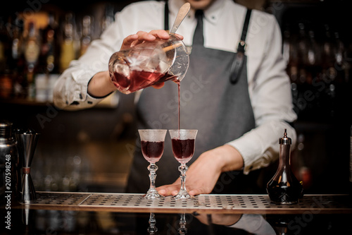 Bartender pouring strong summer Arnaud cocktail into the glasses Canvas Print