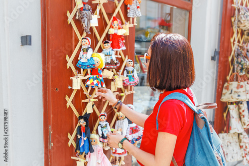 Photo  Woman customer looking at traditional puppets made of wood at the outdoor market