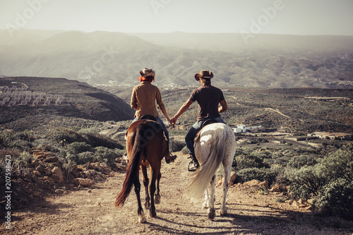 love and friendship concept outdoor for people ride horses in the countryside. amazing landscape and a world to discover traveling together. caucasian man and woman