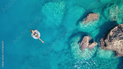 Aerial view at the girl on sea surface. Beautiful composition at the summer time