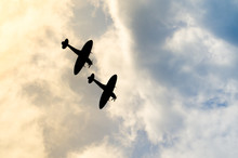 Two Silhouetted Spitfires Dive...
