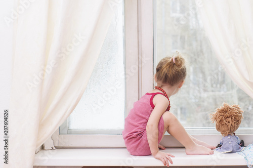 Fotografie, Obraz  Sad little girl with a doll waiting for her mother near the window