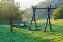 Wooden Children Playground In Highland Green Landscape.
