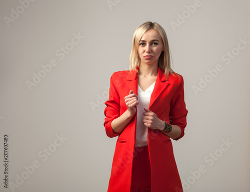 Young Beautiful White Blond Girl In A Bright Red Strict Suit With A