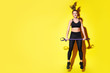 canvas print picture - Young happy fitness girl with sporty body posing at studio on a yellow background. Beautiful fit Girl. Fitness smiling model in black sportswear. Weight Loss. Sporty healthy female. Horizontal