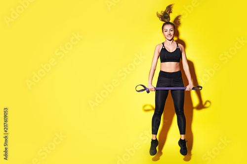 Fotografía  Young happy fitness girl with sporty body posing at studio on a yellow background