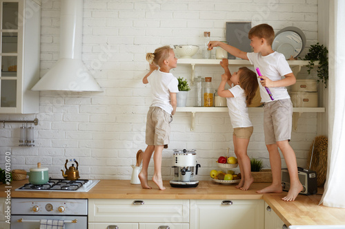 Fototapeta Happy childhood, family, fun and entertainment concept. Candid shot of three children siblings playing together in kitchen standing barefooted on wooden counter, looking for candies on shelf obraz na płótnie