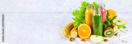 Fotografia  Green, yellow, purple smoothies in currant bottles, parsley, apple, kiwi, orange on a gray table