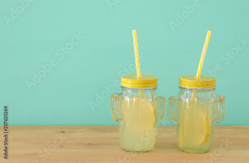 Fotografía  Image of fresh lemonade drink in cute cactus shape glasses over wooden table