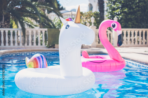 Garden Poster Flamingo Inflatable colorful white unicorn and pink flamingo at the swim pool. Vacation time in the swimming pool with plastic toys. Relaxation and fun concept