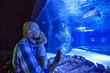 Leinwandbild Motiv Family observing fish at the aquarium