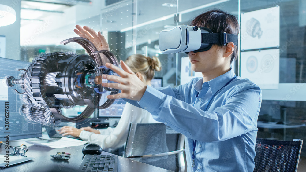 Fototapeta Computer Science Engineer wearing Virtual Reality Headset Works with 3D Model Hologram Visualization, Makes Gestures. In the Background Engineering Bureau with Busy Coworkers.