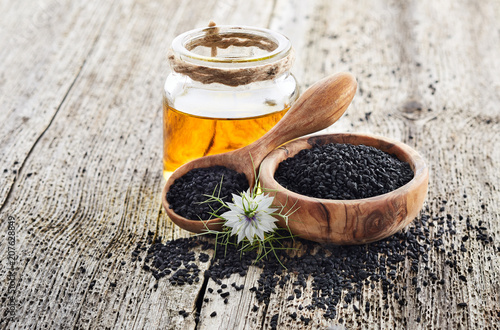 Poster Graine, aromate Black cumin oil with flower on wooden background