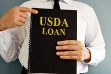 USDA Loan Concept. Man Holding...