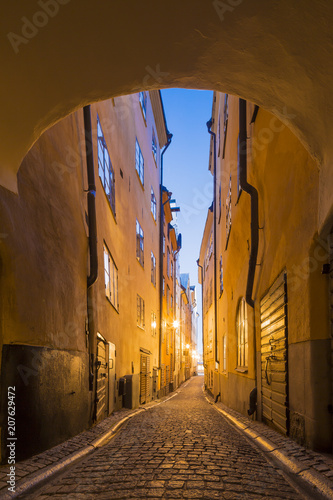 Poster Smal steegje Night view of narrow alley connecting with archway passage street with historic town houses of colored facade illuminated by lights in the Old city (Gamla Stan) of Stockholm, Sweden.
