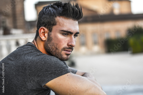 Fotografia  Handsome muscular man with tattoo posing in European city center, Turin, Italy