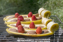 .Fresh Bananas With Strawberries And Chocolate On The Grill. Dessert For A Picnic.