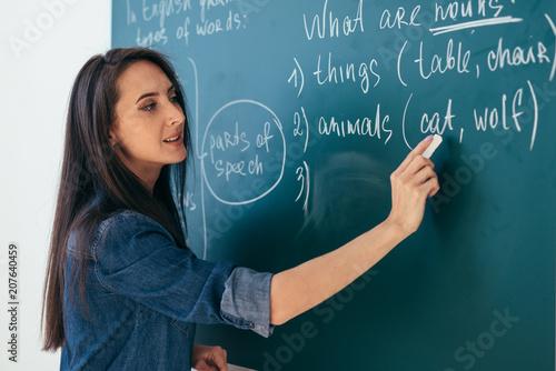 Fotografía  Student or teacher standing in front of the class blackboard