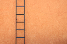 Iron Ladder On Painted Cement Wall.