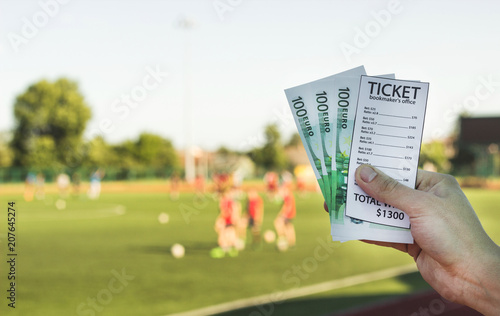 Fotomural  Man is holding a bookmaker's ticket and money euros in the background of a stadi