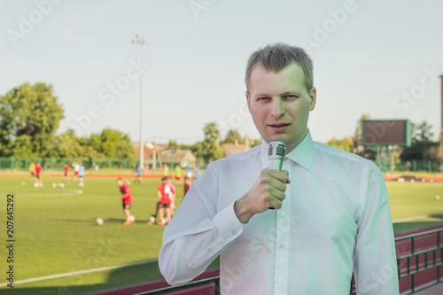 A male commentator in a white shirt with a microphone comments on football in the background of a football match
