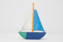 A Wooden Toy Yacht. The Toy Boat Shows Signs Of Use, But The Sails Are In Tact And Still Attached To The Wooden Mast. It Is Painted In 4 Colours With A Simple Keel Indicating This Toy Is Ornamental.