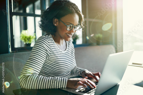 Fotografía  Young African woman smiling and working online with a laptop