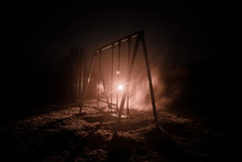 Night Photo Of Metal Swing Standing Outdoor At Night Time With Fog And Surreal Toned Light On Background. Nobody There.