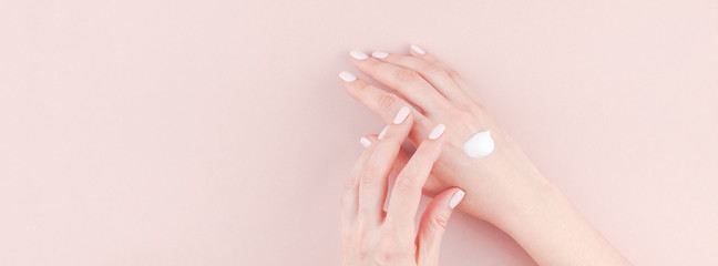 Woman moisturizing her hand with cosmetic cream