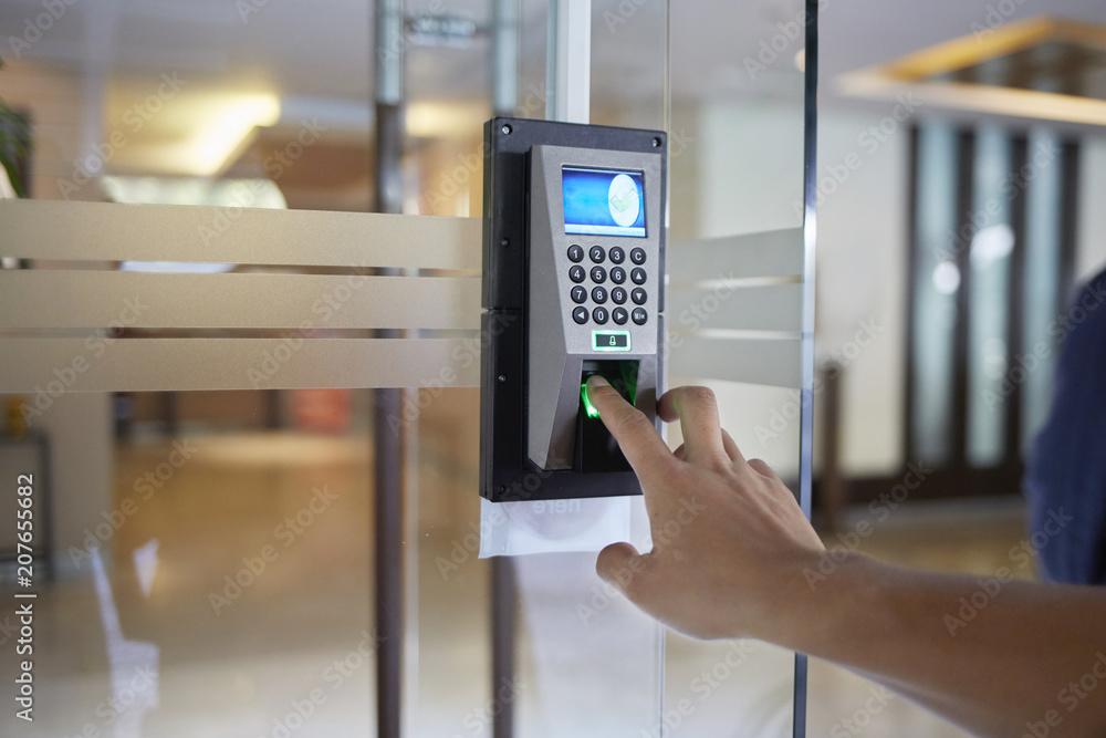 Fototapeta Yong man push finger down the electronic control machine to access the door