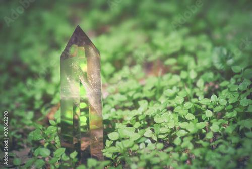 Fotografía  Large mystical faceted quartz crystal on a grass nature background close-up